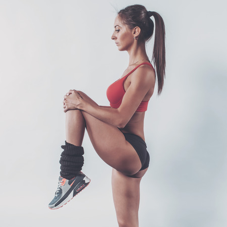 shaping: Portrait of muscular active athlete woman standing looking forward lifting up leg in hands doing exercise warming up working stretching with fitness, sport, training and lifestyle concept.