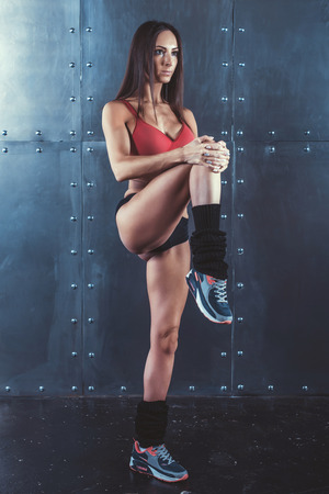 Portrait of muscular active athlete woman standing looking forward lifting up leg in hands doing exercise warming up working stretching with fitness, sport, training and lifestyle concept.