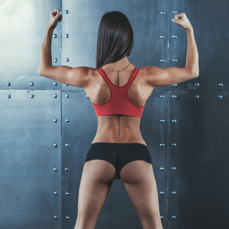 back posing: Muscular active athletic young woman with sexy buttocks showing muscles of the back shoulders and hands fitness, sport, training and lifestyle concept
