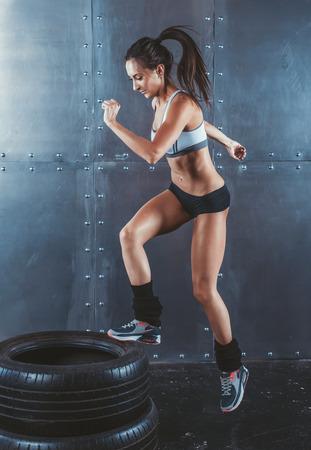 스포티 한 활성 맞는 여자 상자 점프. 여성 운동 선수는 타이어 피트니스, 스포츠, 교육 및 생활 양식 개념을 점프 수행 스톡 콘텐츠