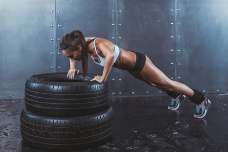 workout: Sportswoman. Fit sporty woman doing push ups on tire strength power training concept crossfit fitness workout sport and lifestyle