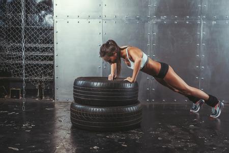 muscle: Deportista. Ajuste deportivo mujer haciendo flexiones sobre la fuerza de los neum�ticos concepto de entrenamiento de la potencia crossfit deporte entrenamiento de fitness y estilo de vida