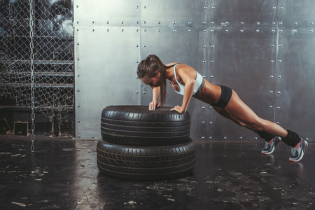 tire: Sportswoman. Fit sporty woman doing push ups on tire strength power training concept crossfit fitness workout sport and lifestyle