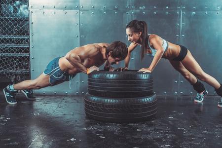 fuerza: Deportista. Ajuste deportivo mujer haciendo flexiones sobre la fuerza de los neumáticos concepto de entrenamiento de la potencia crossfit deporte entrenamiento de fitness y estilo de vida