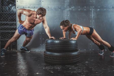 ginástica: Sportswoman. Fit Mulher desportiva que faz push ups em força pneu conceito de treinamento de potência crossfit esporte treino de fitness e estilo de vida Banco de Imagens