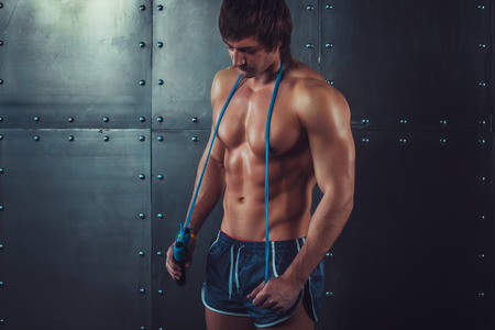 muscle guy: Fitness model muscular man with skipping jumping rope around his neck with copy space healthy lifestyle bodybuilding concept.