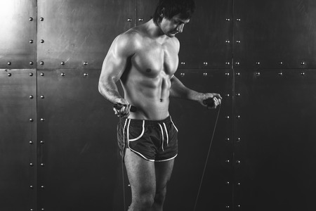 powerlifting: Fitness model muscular man with skipping jumping rope around his neck with copy space healthy lifestyle bodybuilding concept black and white.