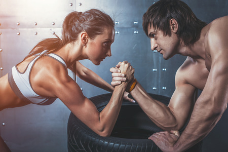 female wrestling: Athlete muscular sportsmen man and woman with hands clasped arm wrestling challenge between a young couple Crossfit fitness sport training lifestyle bodybuilding concept