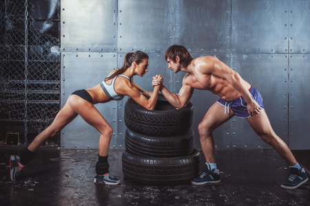 challenges: Athlete muscular sportsmen man and woman with hands clasped arm wrestling challenge between a young couple Crossfit fitness sport training lifestyle bodybuilding concept