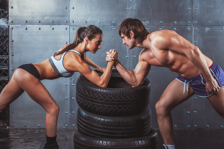 Athlete muscular sportsmen man and woman with hands clasped arm wrestling challenge between a young couple Crossfit fitness sport training lifestyle bodybuilding concept photo