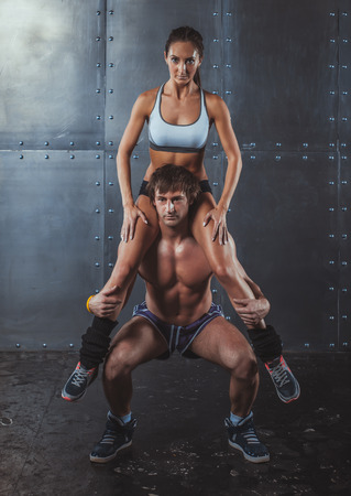 squatting down: Athlete muscular sportsman doing exercising squats with woman sitting on his shoulders Crossfit fitness sport training lifestyle bodybuilding concept
