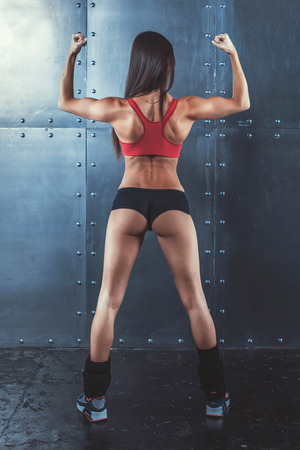 showing muscles: Muscular active athletic young woman showing muscles of the back shoulders and hands fitness, sport, training and lifestyle concept