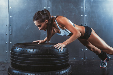 push ups: Sportswoman. Fit sporty woman doing push ups on tire strength power training concept crossfit fitness workout sport and lifestyle