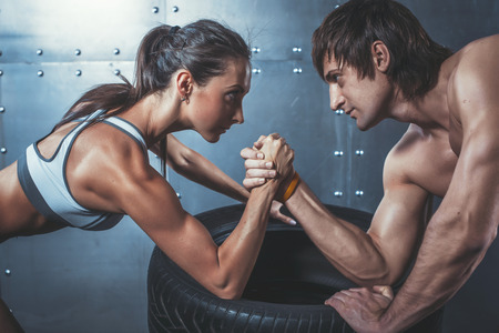 male arm: Athlete muscular sportsmen man and woman with hands clasped arm wrestling challenge between a young couple Crossfit fitness sport training lifestyle bodybuilding concept