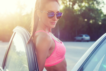 bra model: Athlete sporty fit young woman in sports bra wearing sunglasses standing leaning on car with door open looking at camera Stock Photo