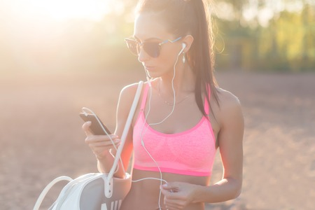 healthy looking: Athlete woman listening music looking at smartphone after workout in nature outdoors portrait summer evening on the beach summer holidays and vacation healthy lifestyle.