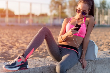 active listening: Beautiful fitness athlete woman wearing sunglasses resting listening music after work out exercising on summer evening in beach at sunset with smartphone outdoor portrait