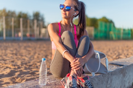 woman work: Beautiful fitness athlete woman wearing sunglasses listening music resting after work out exercising on summer evening in beach at sunset outdoor portrait