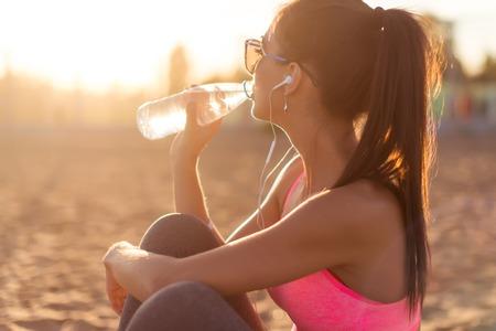 Agua aptitud de la mujer atleta beber hermosa después del trabajo a cabo el ejercicio de la puesta de sol tarde de verano en la playa de Retrato al aire libre Foto de archivo