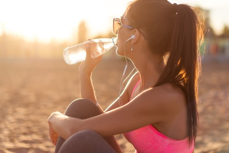drink at the beach: Beautiful fitness athlete woman drinking water after work out exercising on sunset evening summer in beach outdoor portrait Stock Photo