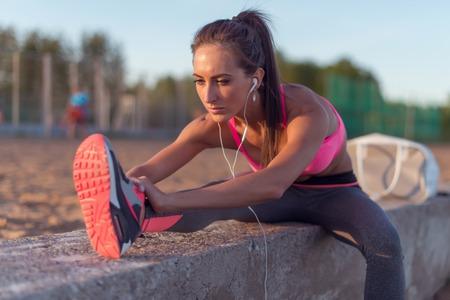 estiramiento: Modelo de la aptitud atleta chica caliente que estira sus músculos isquiotibiales, pierna y espalda. Mujer joven que ejercita con los auriculares escuchando música al aire libre en la playa o campo de deportes en la tarde de verano.