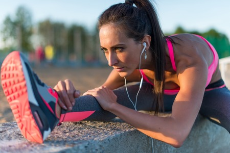 listening back: Athletic woman stretching her hamstring, legs exercise training fitness before workout outside on a beach at summer evening with headphones listening music. Stock Photo