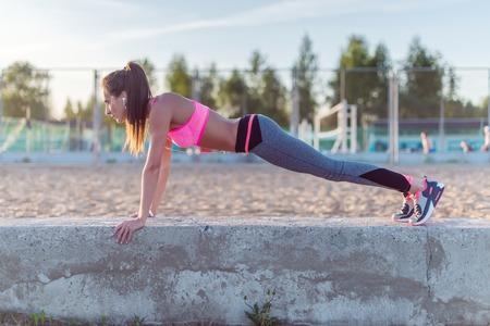 gimnasio mujeres: Mujer de la aptitud que hace pectorales al aire libre sesión de entrenamiento de la vista lateral noche de verano deporte Concepto de estilo de vida saludable