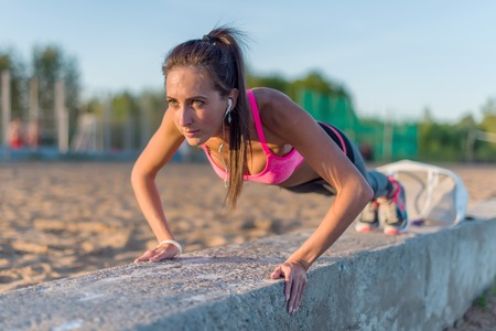 Fitness woman doing push ups Outdoor training workout summer evening. Concept sport healthy lifestyle photo