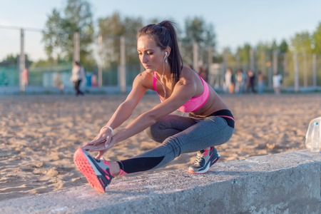 hamstring: Athletic woman stretching her hamstring, legs exercise training fitness before workout outside on a beach at summer evening with headphones listening music