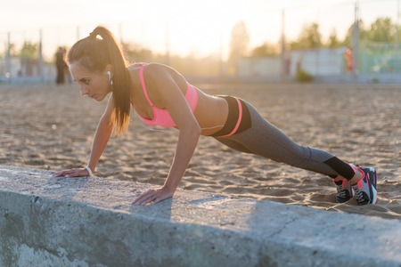 Fitness woman doing push ups Outdoor training workout summer evening. Concept sport healthy lifestyle