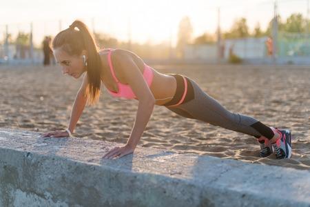 haciendo ejercicio: Mujer de la aptitud que hace pectorales al aire libre sesión de entrenamiento de la tarde del verano. Deporte concepto estilo de vida saludable Foto de archivo
