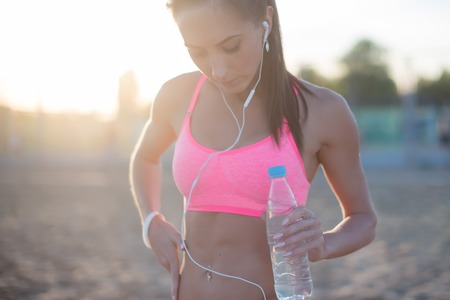 woman work: Beautiful fitness athlete woman resting drinking water after work out exercising on beach summer evening in sunny sunshine outdoor portrait. Stock Photo