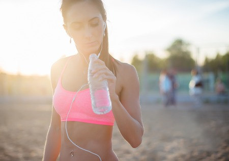 Beautiful fitness athlete woman resting drinking water after work out exercising on beach summer evening in sunny sunshine outdoor portrait. photo