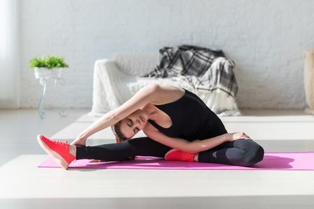 estiramientos: Mujer apta flexibilidad corporal alta se extiende la pierna y la espalda se caliente haciendo ejercicios de gimnasia aeróbic en casa. Foto de archivo