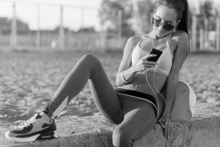 trabalhar fora: Beautiful fitness athlete woman wearing sunglasses resting listening music after work out exercising on summer evening in beach at sunset with smartphone outdoor portrait