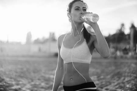 drinks: Beautiful fitness athlete woman resting drinking water after work out exercising on beach summer evening in sunny sunshine outdoor portrait. Stock Photo