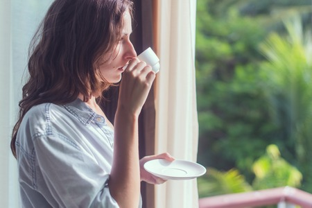 Woman drinking tea or coffe and looking through the window.  Young lady meeting sunrise Stock Photo