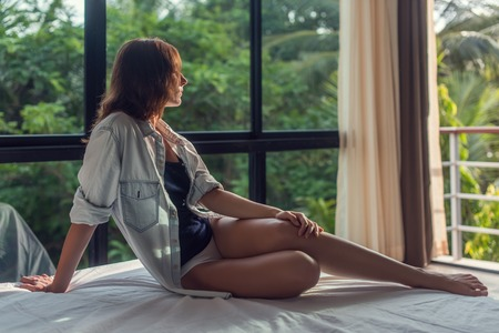 wonderfull: Beautiful young woman is laying on the bad and looking through windows. Pretty lady is watching wonderfull view  on the terrace. Stock Photo