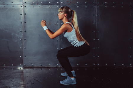 warm up exercise: Athletic young woman fitness model warming up doing squats exercise for the buttocks concept sport slimming healthy lifestyle. Stock Photo