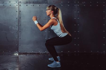 culo: Atletica giovane donna modello di forma fisica in fase di riscaldamento facendo squat esercizio per i glutei concetto di sport che dimagrisce stile di vita sano.