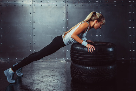 pushup: Sportswoman. Fit sporty athlete woman doing push ups on tire strength power training concept crossfit fitness workout sport and lifestyle side view. Stock Photo