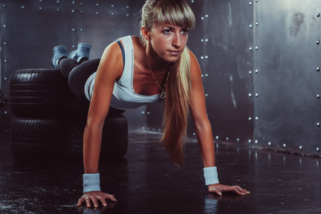 fitness workout: sporty athlete woman doing push ups on tire strength power training concept cross fit fitness workout sport and lifestyle. Stock Photo