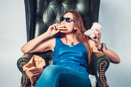 junks: Funny crazy woman eating hamburger junk food and fries sitting in chair