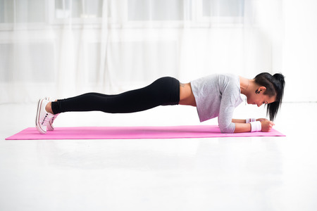 Slim fit girl doing planking core muscles exercise indoors at home in the living room side view fitness healthy lifestyle and diet concept.