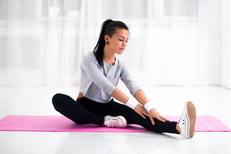 lithe: Fit woman doing aerobics gymnastics stretching exercises her leg and back to warm up at home on yoga mat