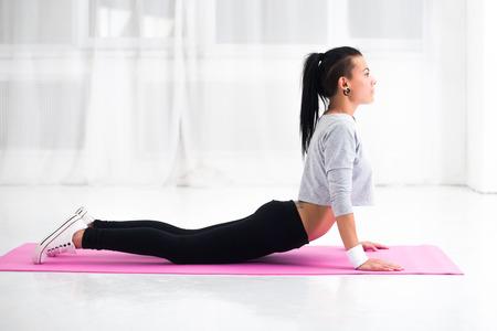arching: Chica haciendo el calentamiento de ejercicios para la columna vertebral, salto mortal hacia atr�s, arqueando su espalda estirar ejercicio en casa o clase de yoga. Foto de archivo