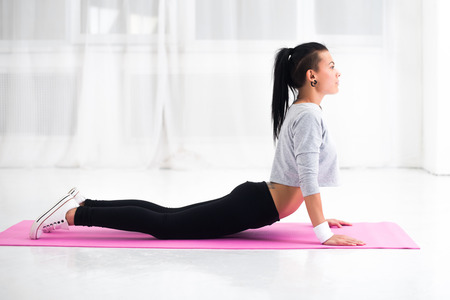 arching: Girl doing warming up exercise for spine, backbend, arching stretching her back  working out at home or yoga class. Stock Photo