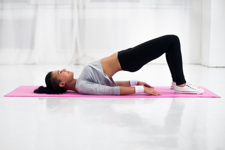 Bridge pose sporty woman doing warming up exercise for spine, backbend, arching stretching her back  working out at home fitness workout yoga gymnastics concept. Banco de Imagens