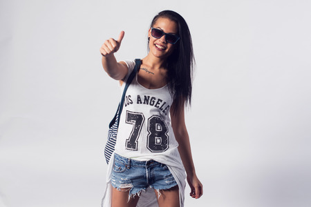 swagger: Young woman in sunglasses showing thumb up looking at camera. Portrait of trendy girl having fun style casual concept lifestyle urban fashion. Stock Photo