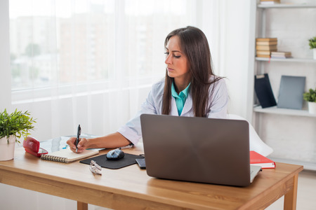 adult writing: Portrait of physician doctor working in medical office workplace writing prescription sitting at desk Stock Photo
